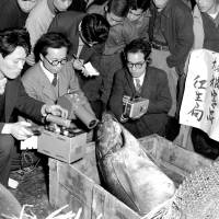 A file photo from March 16, 1954, shows officials measuring radiation levels of a tuna that had been brought to the Tsukiji fish market in Tokyo from the Fukuryu Maru No. 5. | KYODO