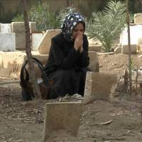 A photo provided by Megumi Ito shows Nahoko Takato praying before the grave of an Iraq War victim in a scene from the movie 'Fallujah.' | CHUNICHI SHIMBUN