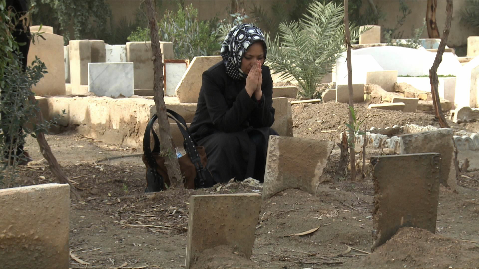 A photo provided by Megumi Ito shows Nahoko Takato praying before the grave of an Iraq War victim in a scene from the movie 'Fallujah.'   CHUNICHI SHIMBUN