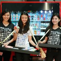 Models show off 'kawaii' (cute) Japanese products in front of a vending machine Friday in Singapore. Fashion brand and retailer Satisfaction Guaranteed began selling the products last weekend. | KYODO