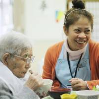Charito Ito, a Filipino caregiver, helps an elderly woman eat her meal at a care home in Kesennuma, Miyagi Prefecture, in January. | KYODO