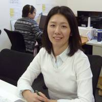Matchmaker: Akiko Nishiura, the president of Nokisaki Inc., poses on Jan. 7. Her Tokyo-based company connects individuals looking for parking spots near popular destinations with people who have open parking space available at homes, businesses or other places. | KYODO