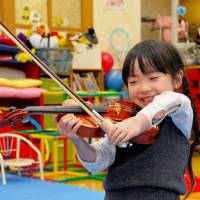 Youthful promise: Five-year-old Yuna Kodama, who was born without her left arm below the elbow, practices the violin with a myoelectric prosthesis in November.   KYODO