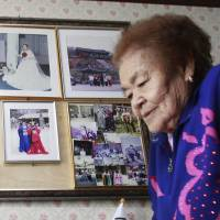 Telling her story: Kim Gun-ja, 89, a former 'comfort woman' forced to provide sex for Japanese troops during the war, passes by her wedding picture (top center) at the House of Sharing, a nursing home and museum for 10 ex-sex slaves.   AP
