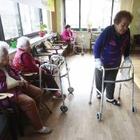 Kim (right) passes by other comfort women Yi Ok-seon, 88 (far left) and Kim Wei-han, 86.   AP