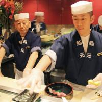 Losing touch: Toshiaki Toyoshima (left), owner of Sushi Gen, watches one of his chefs make sushi while wearing gloves at his Los Angeles restaurant Feb. 4. | KYODO