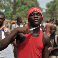Separatist tendencies: A man holds a knife to his throat while claiming to be looking for Muslims to cut off their heads in Bangui, the capital of the Central African Republic, on Sunday. | AFP-JIJI