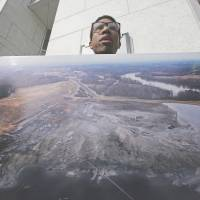 Coal water: A protester holds a photo of a Duke Energy coal plant during a rally Feb. 6 at the company's headquarters in Charlotte, North Carolina. Duke Energy estimates up to 82,000 tons of ash were released from a broken storm water pipe at its Dan River power plant.  | AP