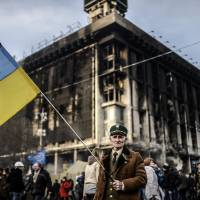 A man holds a Ukrainian flag in Kiev on Wednesday as interim pro-Western leaders worked out a new Cabinet in the splintered nation.  | AFP-JIJI