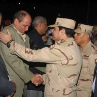 In good hands?: Egyptian Defense Minister Gen. Abdel-Fattah el-Sissi (center) consoles a man at a funeral for several military personnel who were killed when a helicopter crashed in the Sinai Peninsula. An al-Qaida-inspired group based in the Sinai has claimed responsibility for bringing down the helicopter in the lawless desert region. | AP