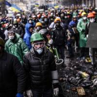 Anti-government protesters stand behind barricades during a face-off with riot police Thursday in Kiev. The scale of this week's bloodshed, three months into Ukraine's political crisis, shocked the West and was condemned as an attempted coup by Russia. | AFP-JIJI