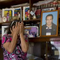 Bitter loss: A woman weeps next to a portrait of her son, who was kidnapped and murdered, in Yautepec, Mexico, on Feb. 5. | AP