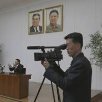South Korean Kim Jung-wook (center) confesses to 'anti-state' crimes Thursday in Pyongyang, seated under the portraits of late North Korean leaders Kim Il Sung (left) and Kim Jong Il. | AP