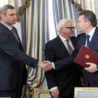 Ukraine President Viktor Yanukovich shakes hands with opposition leader Vitali Klitschko (left) as German Foreign Minister Frank-Walter Steinmeier stands in the background after the signing of an EU-mediated peace deal with opposition leaders in Kiev on Friday. | REUTERS