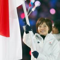 Japanese curler Ayumi Ogasawara carries the nation's flag. | AP, KYODO/GETTY