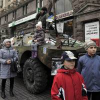 Children stand in front of an armored vehicle, formerly used by Ukraine's security forces, in Kiev on Monday. | AFP-JIJI