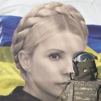 Past and present: A uniformed anti-government activist walks past a poster depicting jailed former leader Prime Minister Yulia Tymoshenko in Kiev on Friday.  | AP