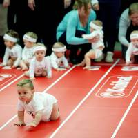 Parents race toddlers against each other during the Nine Months Fair, held to provide information about pregnancy and babies, in Amsterdam on Wednesday. | AFP-JIJI