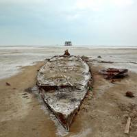 Solidified salt and sand surround the wreckage of a boat in Iran's Lake Oroumieh. | AP