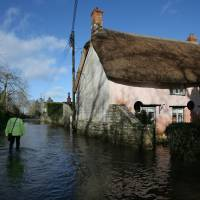 Flow of history: An emergency support worker wades through the village of Thorney in Somerset, England, on Sunday. | AP