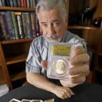 David Hall, co-founder of Professional Coin Grading Service, is seen with some of the1,427 Gold Rush-era gold coins at his office in Santa Ana, California, on Tuesday. A California couple stumbled across the rare, mint-condition coins buried in the shadow of an old tree.   AP