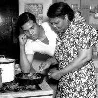 Boxer Joe Louis, the world heavyweight champion from 1937 to 1949, watches his mother, Lila Brooks, fry chicken at home in Detroit in this undated photo.   AP