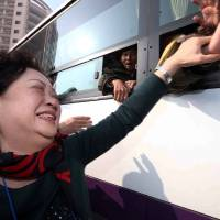 A South Korean woman cries while holding her North Korean father's hand as his bus leaves a reunion at Diamond Mountain in North Korea on Tuesday. | AP