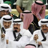 Rules of order: Saudi Arabian King Abdullah (center) and his half brother, Interior Minister Prince Nayef bin Abdul Aziz al-Saud (right), take part in the traditional Arda war dance during the Janadriyah Festival of Heritage and Culture in Riyadh on March 23, 2010. | AP