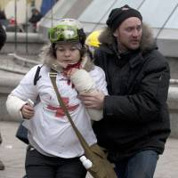 A woman is helped after being shot in her neck by a sniper bullet, in Kiev's Independence Square, the epicenter of the country's current unrest, on Thursday. | AP