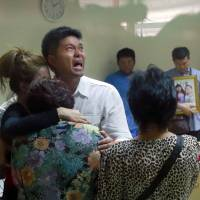 Tayakorn Yos-ubon, the father of two children killed a grenade attack at an anti-government protest site in Bangkok on Sunday, is embraced by family members Monday as he cries during a visit to a hospital to collect their bodies.   AP