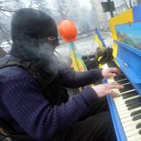 Facing the music?: A masked anti-government activist plays a piano set on a barricade in Kiev during a concert organized for the protesters and policemen Monday. | AFP-JIJI