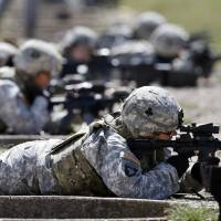 Female U.S. soldiers train on a firing range while wearing new body armor at Fort Campbell, Kentucky, in September 2012. | AP
