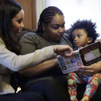 Word count: Caseworker and home visitor Stephanie Taveras (left) reads a book with Ashley Cox and Cox's 16-month-old son, Jaiden, at the family's home in Providence, Rhode Island, on Feb. 3. | AP