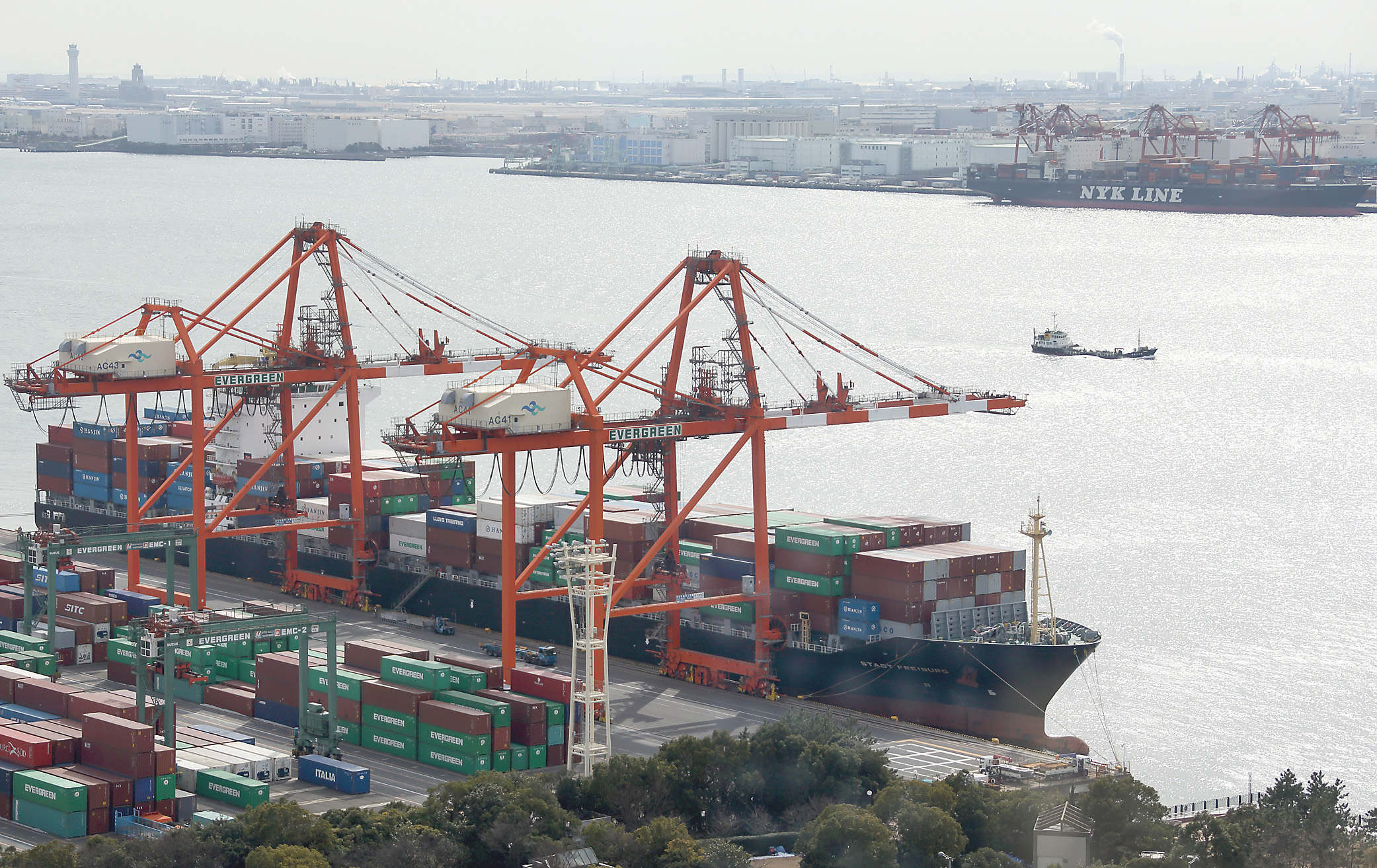 A containership sits berthed next to gantry cranes at a shipping terminal in Tokyo on Wednesday. Japan's trade deficit widened to a record in January as surging import costs weigh on Prime Minister Shinzo Abe's campaign to drive a sustained recovery. | BLOOMBERG