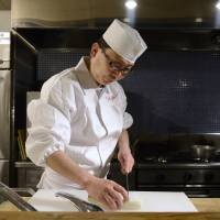 The right ingredients: Shintaro Esaki, a Michelin-starred chef, prepares food at his Aoyama Esaki restaurant in Tokyo on Jan. 28. Osamu Ito, a former Morgan Stanley MUFG Securities Co. banker, is setting up a crowdfunding company that will raise money for startups such as Esaki's 'bento' boxed meals business. | BLOOMBERG