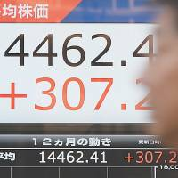 Rebound: A man walks past a price quotation board displaying the Nikkei stock average in front of a securities company in Tokyo on Friday. | AFP-JIJI