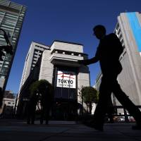 A pedestrian walks past the Tokyo Stock Exchange on Dec. 24, 2013. | BLOOMBERG