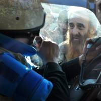 Power of hunger: A man peers into the vehicle of a United Nations staff member on Feb. 9 before being evacuated from the Syrian city of Homs. | AFP-JIJI