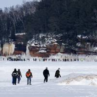 Worth the hike: People walk across ice to Apostle Islands caves on Feb. 2. | AP