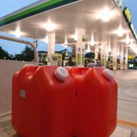 Containers of kerosene stand outside a gasoline station in the city of Chiba. | BLOOMBERG