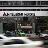 Heavy traffic: Mirage vehicles are displayed outside the Mitsubishi Motors Corp. headquarters in Tokyo last April 24. | BLOOMBERG