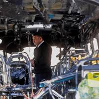 An Egyptian policeman inspects a damaged bus on Monday following an attack by a suicide bomber the day before near Taba, a town on the Egypt-Israel border. | AP
