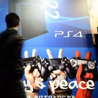 A visitor looks at posters of Sony's PlayStation 4 video game console on Feb. 1 during the 'Try! PlayStation 4!-2.22-' event at Ginza Sony building in Tokyo. | AFP-JIJI