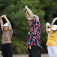 Looking to the future: Elderly people participate in NHK's morning radio exercise program in a Tokyo park in September 2012. Amid rising demand for senior-tailored housing, Sumitomo Mitsui Banking Corp. is seeking to buy about ¥10 billion in senior housing properties before taking its health-care real estate investment trust public. | BLOOMBERG