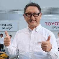 Rolling in it: Akio Toyoda, president of Toyota Motor Corp., signals his satisfaction in a photo with drivers and members of Toyota Motorsport GmbH (TMG) during a news conference in Tokyo last week. | BLOOMBERG