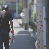 Falling behind: A man walks toward a labor and welfare center in Tokyo. As workers' wages struggle to keep up with the recent surge in 'bad inflation,' Prime Minister Shinzo Abe's economic strategies face a litmus test, pundits say.   BLOOMBERG