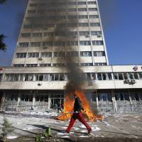 War on bad business: A protester walks past a fire in front of a government building in Tuzla, Bosnia, on Feb. 7.   AP