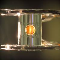 A pinch of sun: A fusion fuel capsule is seen through a hole in its energy-focusing confinement chamber in this photo provided by the journal Nature on Tuesday. | AFP-JIJI