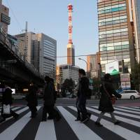One-way street: Tokyo Electric Power Co.'s headquarters building is seen in the background as people cross a street in the capital last month. | BLOOMBERG