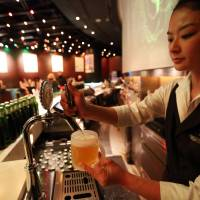 Have a cold one: A bartender fills a glass with Kirin Holdings Co.'s Heartland beer at a bar in the Roppongi Hills complex in Tokyo on April 17, 2013.   BLOOMBERG